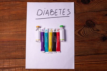Diabetes sign on a white paper with insulin ampoules, colorful sugar sticks on wooden background, World diabetes day concept.Prevent disease before it begins,detection diagnosis, patients list mockup.