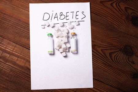 Diabetes sign on a white paper with insulin ampoules, sugar cubes on wooden background, World diabetes day.Prevent disease before it begins,detection diagnosis,clinical researches,patients list mockup Stok Fotoğraf