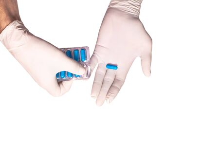 Male doctors hands in rubber gloves holding a plate of blue pills on white backgound isolated. Concept sterility purity, medical clinic, laboratory, glove on the hand of a nurse. Diabetes treatment.