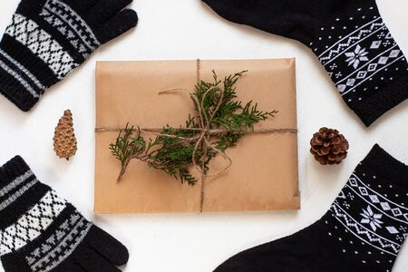 New year 2020 flatlay. Christmas black ornamental socks and gloves, gift box in eco kraft paper. Mock up template design. Winter holiday decorations,pine cones,minimal style,white background. Top view