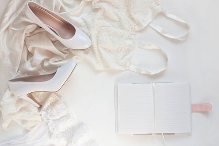 Wedding flat lay, womans stylish fashion accessories in biege colors on white background,copy space. Bridal details concept, silk lace dress, notebook mockup, fashion shoes,trendy composition,top view Reklamní fotografie