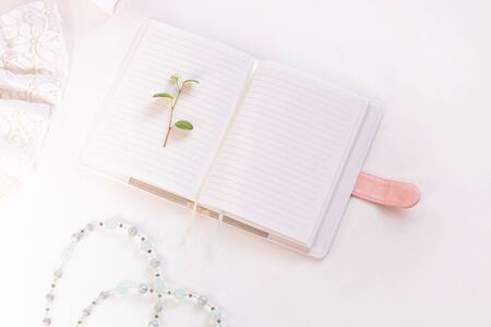 Wedding flat lay, blank notebook mockup, womans stylish accessories in biege colors on white background,copy space. Bridal details concept, silk lace dress, fashion shoes,trendy composition,top view.