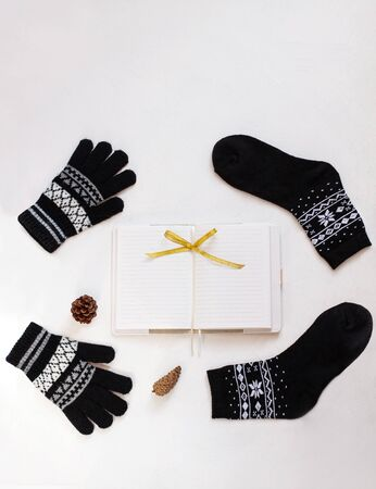 New year 2020 flatlay. Christmas black ornamental socks and gloves, blank notebook with ribbon bow. Mockup template design. Winter decorations, pine tree cones,minimal style,white background. Top view Stok Fotoğraf