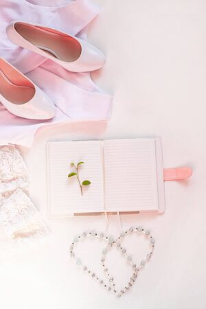 Wedding flat lay, womans stylish accessories in biege pink colors on white background,copy space. Bridal details concept, silk lace dress, notebook mockup, fashion shoes,trendy composition, top view.