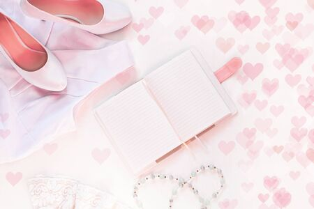 Wedding flat lay, womans stylish accessories in pink colors on white background bokeh lights,copy space.Valentines card, bridal concept,notebook mockup, fashion dress,shoes,trendy composition,top view