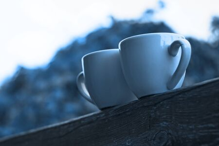 Two cups of coffee in classic blue color of the Year 2020 on wooden balcony on the background of sunset with beautiful bokeh lights.Valentines card.Love, romantic. White mugs of hot drinks.Copy space.