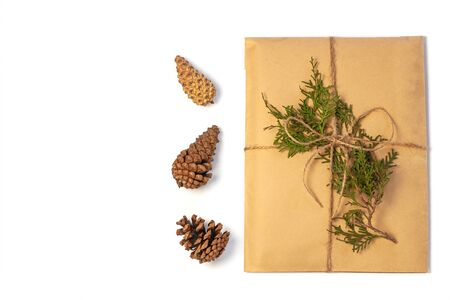 Eco gift box wrapping in kraft paper on white background isolated. Vintage eco-friendly natural style. A present with Christmas tree branch,pine cones. Top view composition,New year flatlay,copy space Stok Fotoğraf