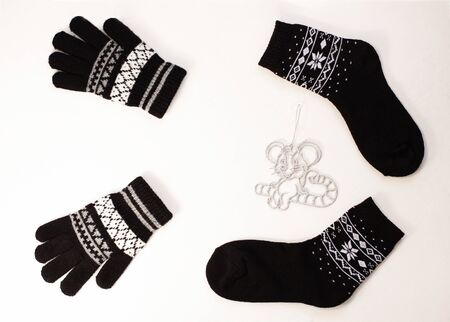 New year 2020 flatlay. Christmas black ornamental socks, gloves and silver rat on lollipop candy. Mock up template design. Winter holiday decorations,pine cones,minimal style,white background.Top view Stok Fotoğraf