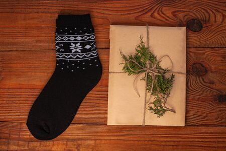New year 2020 flatlay. Christmas black ornamental socks and trendy gift box in eco kraft paper. Mockup template design. Winter holiday decorations,pine cones, minimal style,wooden background.Top view.