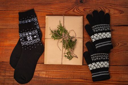 New year 2020 flatlay. Christmas black ornamental socks and gloves, gift box in eco kraft paper. Mockup template design. Winter holiday decorations,pine cones,minimal style,wooden background.Top view.