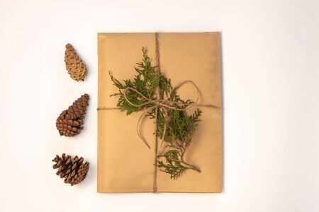 Eco gift box wrapping in kraft paper on white background isolated. Vintage eco-friendly natural style. A present with Christmas tree branch and pine cones. Top view composition,New year flatlay,mockup