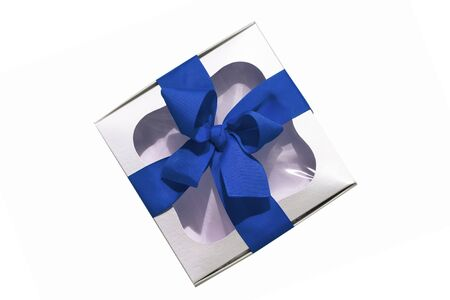 Trendy silver gift box with blue ribbon bow isolated on white background. Stylish metallic present box with transparent window. Contrasting web banner mockup. Advertising flatlay,top view, copy space.