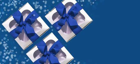 Trendy silver gift boxes with ribbon bow isolated on blue background with bokeh lights. Stylish metallic present box, New year 2020 site header. Web banner, mockup. Advertising flatlay,top view, copy space.