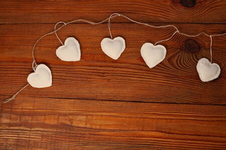 Eco linen fabric hearts on wooden background,Valentines Day concept design.Decorative white heart on crafts jute twine garland,natural retro burlap string. Hand made decorations for lovers day,flatlay Stok Fotoğraf