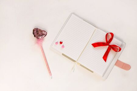 Valentine flatlay. Blank diary, pink heartshaped sequins pen with feathers and ribbon bow on white background. Notebook mockup, cute girlish style. Space for wishes text, sign. Lovers day, 8 march. Stok Fotoğraf