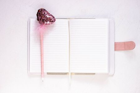 Valentine flatlay. Blank diary, pink heartshaped sequins pen with feathers on white background. Notebook mockup in cute girlish style. Space for romantic wishes text, sign. Valentines day, 8 march.