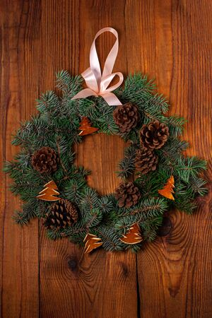 Christmas wreath flatlay. Green spruce branches decorated with orange zest, lights, pine cones and ribbon bow on wooden background,rustic style.New Year 2020 concept.Hand made eco-friendly decorations