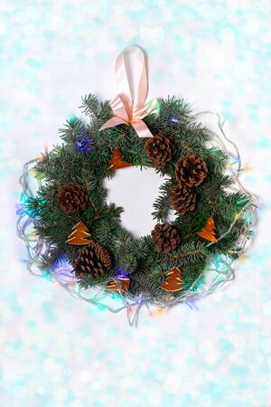 Christmas wreath flatlay. Green spruce branches decorated with orange zest, lights, pine cones and ribbon bow on white background,festive style.New Year 2020 concept.Hand made eco-friendly decorations