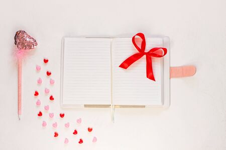 Valentine flatlay. Blank diary, pink heartshaped sequins pen with feathers, herts and ribbon on white background. Notebook mockup, cute girlish style. Space for wishes text, sign. Lovers day, 8 march.