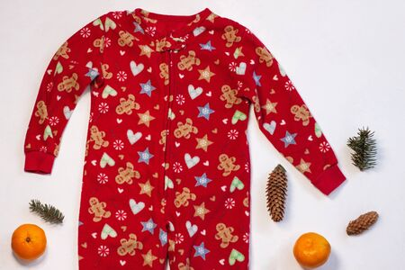 Christmas holidays sweater on white background flatlay. New year events celebration style clothes, cute red warm kids party costume, sleep and play suit. Orange tangerines and spruce cones, top view.