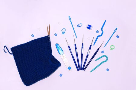 Knitting and crocheting flatlay.Blue yarn skein, crochet hook, row counter on white background isolated.Knit hat process Reklamní fotografie