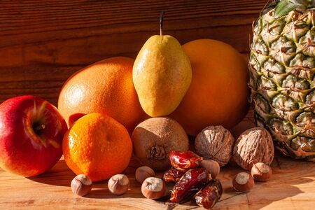 Tropical fruits and nuts vegan diet. Pineapple, grapefruit, orange, pear, walnuts on wooden background,weight loss foods Stock fotó