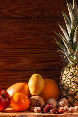 Tropical fruits and nuts vegan diet. Pineapple, grapefruit, orange, pear, walnuts on wooden background. Healthy weight loss food ingredients. Minimal style. Healthful fats, dietary fiber, vitamins. Stock fotó