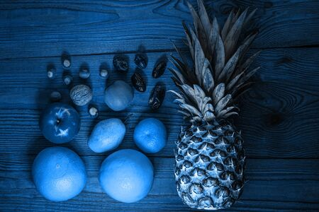 Blue tropical fruits and nuts flatlay. Color trends 2020 background. Healthy weight loss food. Minimal style. Creative social media banner, advertising photo.
