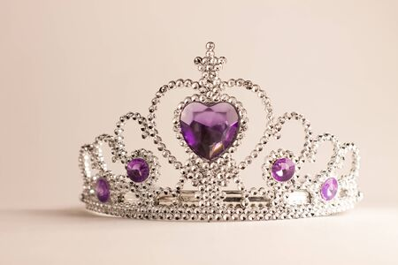 Silver crown with violet heart diamonds isolated on light background. Purple crystal headband. Female Little miss rhinestone tiara. Girl fashion, cute baby style. Kids accessories for birthday party.