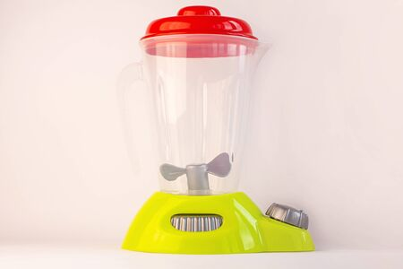 Kids blender on a white background. Childs toy plastic food with drink cup. Healthy eating, raw smoothie, vegan diet, playing with babies. Parents teach children to build good habits.Kitchen play set.