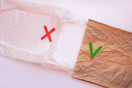 Blank plastic bag vs brown recyclable paper pack. Say no to plastic. Reduce, reuse and recycle concept. Eco friendly kraft bag and ugly synthetic packet, ecology problem. Flat lay on white background. Stock Photo