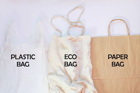 Plastic bag vs paper pack vs fabric eco bag. Say no to plastic. Reduce, reuse and recycle concept. Eco friendly brown recyclable kraft packaging and ugly synthetic packet, ecology problem. Flat lay. Stock Photo