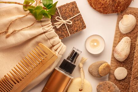 Spa and wellness concept, natural coffee scrub soap, oil cosmetics spray, peeling sand stone,towel,natural wood haircomb