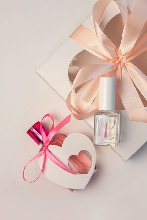 Valentines Day creative concept flat lay. Gift box mockup, pink perfume bottle and nail polish with heart card tag ribbon on white background. Top view copyspace.Celebration 8 march present.Web banner Banque d'images - 138465498