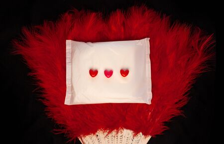 Irregular period concept. Menstrual cycle pad with feathers fan and red hearts on black background. Menorrhagia or heavy menstruation bleeding. Feminine critical days hygiene.Creative minimalism photo
