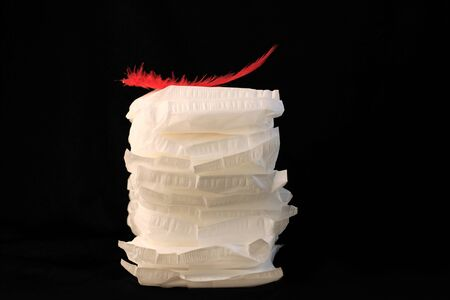 White sanitary individually wrapped napkin pads in stack with red feather on top, black background. Menorrhagia, heavy menstruation. Menstrual critical days hygiene. Irregular period creative concept.