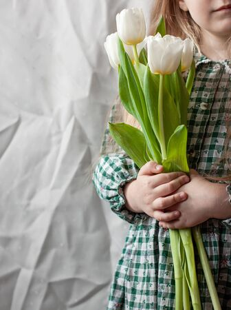 Cute blonde child girl with a bouquet of white tulips in hands faceless. Mothers day, spring concept. Pretty toddler wearing a dress with long hair holding blooming flowers banner. Rustic retro style.