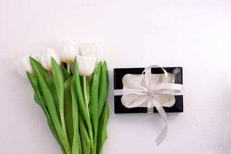 White tulip flowers and black gift box on light background flat lay. Place for text 8 March Happy Womens Mothers Day.Flower Bouquet with silver ribbon, greeting card.Copy space website banner top view Reklamní fotografie