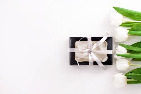 Spring website header template. White tulip black gift box with silver ribbon on light background flat lay. Bouquet greeting card. Copy space banner top view Banque d'images - 140629180