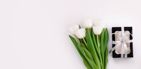 Spring website header template. White tulip black gift box with silver ribbon on light background flat lay. Bouquet greeting card. Copy space banner top view Banque d'images - 140629889