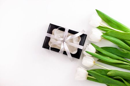 Spring website header template. White tulip black gift box with silver ribbon on light background flat lay. Text place 8 March Happy Mothers Day Sales.Bouquet greeting card. Copy space banner top view