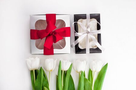White tulips, black and silver gift boxes with ribbons on light background flat lay. Text place 8 March Happy Mothers Day Sales.Bouquet greeting card. Copy space banner.Spring website header template. Banco de Imagens