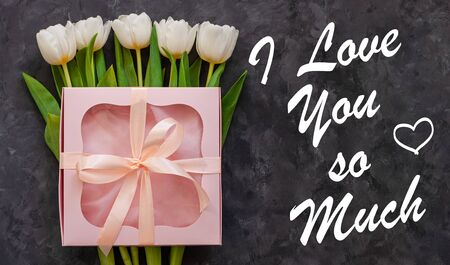 I Love You So Much card sign text. White tulip flowers and pink gift box with ribbon bow on dark background flat lay. Female flower Bouquet greeting card. Copy space website banner top view. Banco de Imagens