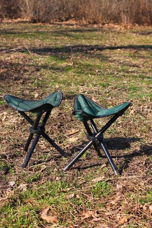 Two camp chairs on green nature background. Picnic on a sunny weather, family day rest, vacations concept. Tourist fishing equipment for adventure, relaxing store advertising banner.Copy space, mockup