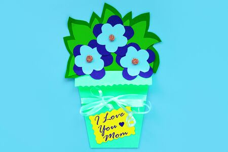 Blue paper flowers with leaves in a basket on a purple background and greeting card tag with I Love You Mom sign. Floral arrangement. Kids handmade craft flower. Spring Mothers day banner flat lay.