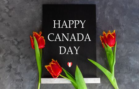 Happy Canada Day text written in a chalkboard and heart with red and white flag colors on grey concrete background with fresh tulips. Canadian banner concept. Blooming flowers flat lay greeting card.