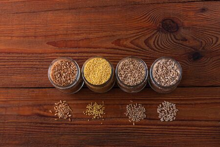 Cereal grains in glass jars on wooden background. Collection of different groats top view barley, oats, millet and wheat. Wholegrain foods with high fiber content flat lay. Healthy diet ingredients.