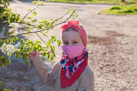 Little girl wearing pink protective face mask against COVID-19 coronavirus disease on the nature with blooming trees during quarantine.Stop epidemic.Pretty child in surgical protection on empty street Archivio Fotografico