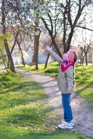 Little girl wearing pink protective face mask against COVID-19 coronavirus disease on the nature with blooming trees during quarantine.Stop epidemic.Pretty child in surgical protection on empty street Stok Fotoğraf