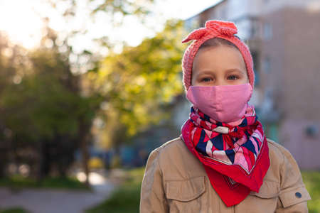 Little girl wearing pink protective face mask against COVID-19 coronavirus disease on the nature with blooming trees during quarantine.Stop epidemic.Pretty child in surgical protection on empty street Reklamní fotografie